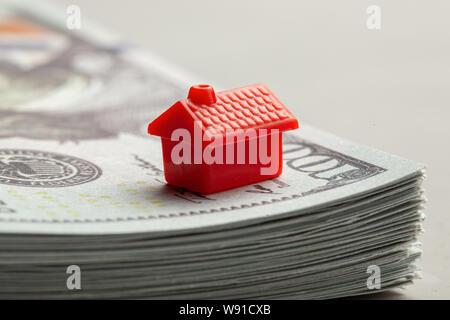Rotes Haus auf einem Stapel Geld. Das Konzept von Steuern oder Immobilien Darlehen. Stockfoto