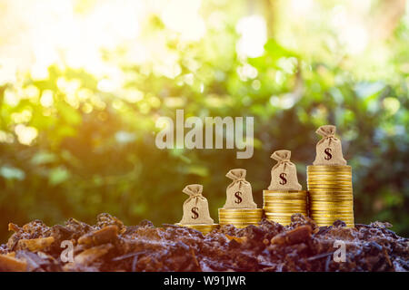 Geld verdienen und Geld Investitionen Konzept. Eine Geld-Beutel auf sich Stapel von Münzen auf die gute Erde und Natur Hintergrund mit Sonnenlicht. Zeigt langfristige