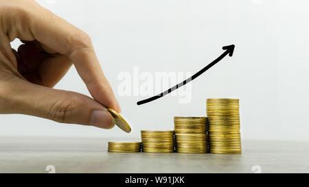 Geld verdienen und Geld Investitionen Konzept. Ein Geschäftsmann Hand Münze über der Münzen auf Holz Tisch Stapel mit steigenden Pfeil. Zeigt langfristige Inve - Stockfoto