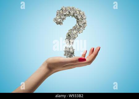 Weibliche Hand, die Dollar Fragezeichen auf blauem Hintergrund - Stockfoto