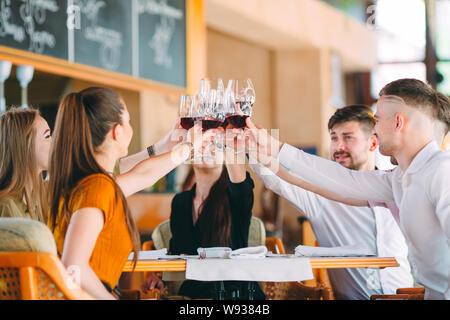 Freunde trinken Wein auf der Terrasse des Restaurants. - Stockfoto