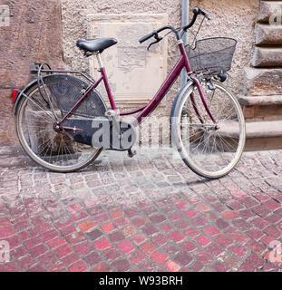 Altes rotes Fahrrad mit Korb, der an die alte Mauer an der Ziegelsteinstraße gelehnt ist - Stockfoto