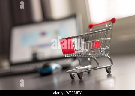 Online-Shopping Konzept: Miniatur Warenkorb, Laptop und Maus im verschwommenen Hintergrund - Stockfoto