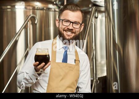 Vorderansicht des Happy bärtige männliche Brauer halten Glas dunkles Bier in der Hand, mit Blick auf die Kamera und lächelnd. Mann in der Brauerei arbeiten und die Prüfung der Qualität der Ale. Konzept der Fertigung. - Stockfoto