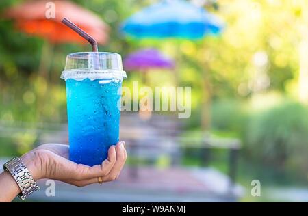 Hand mit einem Glas italienischem Soda kalt Hintergrund verschwommen Ansichten. - Stockfoto