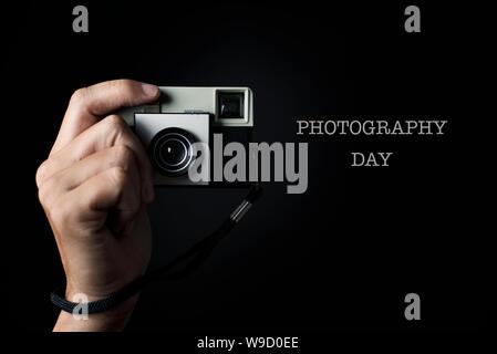 Die Hand eines Mannes über den Auslöser betätigen, um von einem retro Film Kamera, zeigen auf den Beobachter, und der Text fotografie Tag - Stockfoto