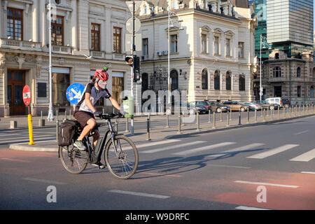 Radfahrer mit Helm, Kamera und oben, Verschmutzung Maske kreuzt Straße auf Radweg in der Innenstadt von Bukarest, Rumänien, - Stockfoto