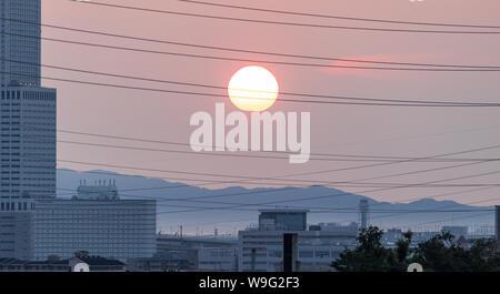 Sonne durch elektrische Drähte über urbane Landschaft - Stockfoto