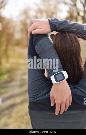 Smartwatch Frau läuft mit Pulsmesser. Nahaufnahme der weiblichen Handgelenk tragen smart Sportuhr als Activity Tracker im Freien während cardio Workout. Fitness Mädchen Dehnung triceps während des Trainings. - Stockfoto