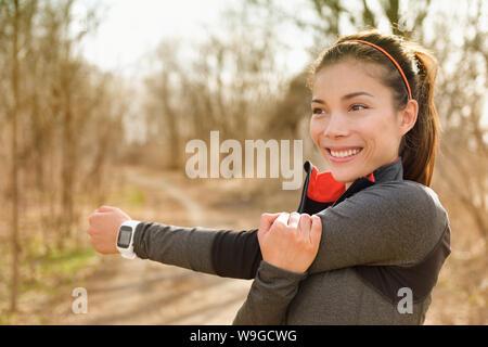 Fitness Frau stretching Arme mit smartwatch vor der Ausführung oder cardio Workout. Gerne asiatische Mädchen tun Aufwärmen vor Joggen mit Pulsmesser in outdoor Park im Herbst. - Stockfoto