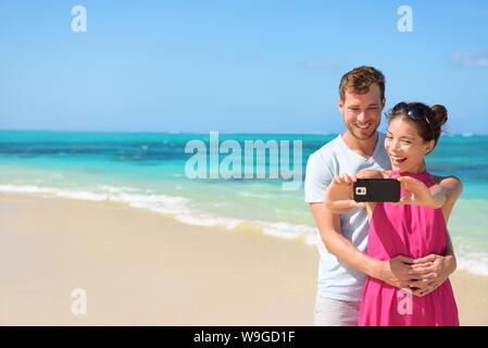 Glückliche junge Multiethnischen Paar unter selfie auf Handy am Strand. Liebevolle Partner sind zusammen, und klicken Sie auf die Bilder. Touristen sind zusammen am Strand genießen. - Stockfoto