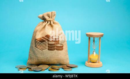 Geld Beutel mit Münzen und eine Uhr/Sanduhr. Zeit-management und Vertrieb. Konzept der Geld sparen. Die arbeitsplanung. Unternehmensstrategie und investme