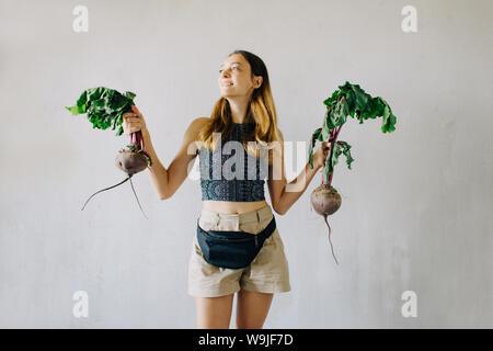 Junge hübsche Mädchen halten frische organische Zuckerrüben auf grauem Hintergrund, Sommer essen - Stockfoto