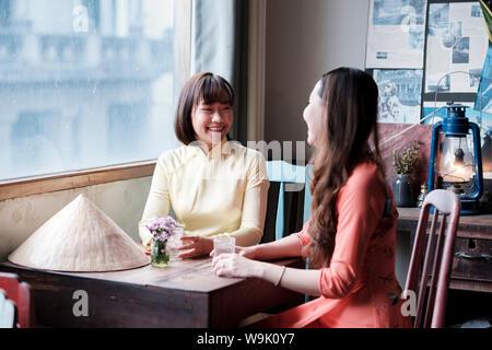 Zwei Freunde in Ao Dai kleider Kaffee in einem Kaffeehaus, Saigon, Ho Chi Minh City, Vietnam, Indochina, Südostasien, Asien - Stockfoto