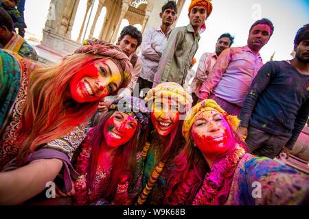 Weibliche Touristen stehen vor Tempel während das Pigment wirft Holi Festival, Vrindavan, Uttar Pradesh, Indien, Asien - Stockfoto