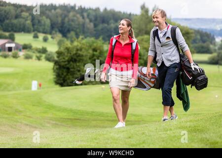 Golf spielenden Paar zusammen auf Golfplatz - Stockfoto