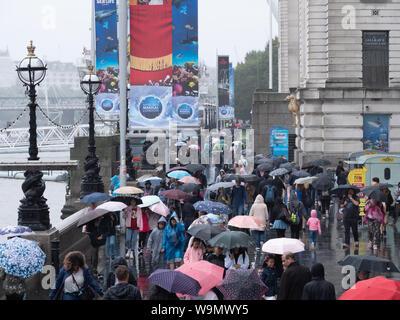 London, Großbritannien. 14. August 2019. Touristen sind nicht durch den Regen hier gesehen auf der Londoner South Bank in der Nähe von London Eye, das am frühen Abend. Credit: Joe Kuis/Alamy Nachrichten - Stockfoto