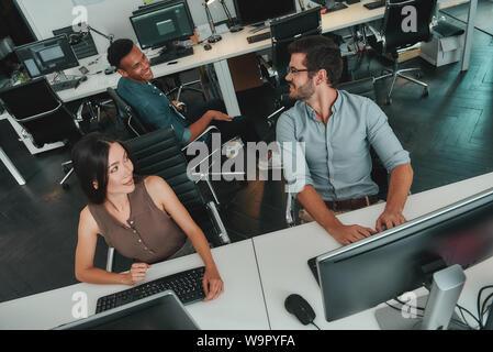Blick von oben auf die junge Geschäftsleute arbeiten an Computern und miteinander reden während der Sitzung in moderner, offener Raum. Job Konzept. Geschäftsleute. Arbeitsplatz