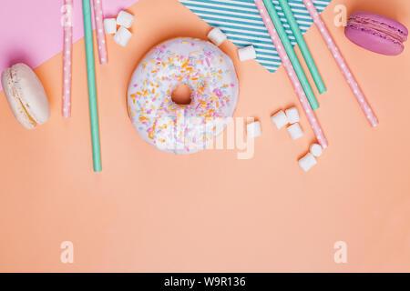 Crwative Komposition mit süßen Leckereien und Party Einrichtung. Donuts, Macarons, Marshmallows und Papier Trinkhalme auf pastellfarbenen Hintergrund - Stockfoto