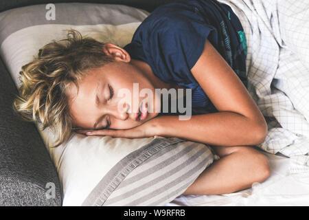 Junge Schlafen mit den Händen auf das Kissen. Schönes Kind schläft alleine im Bett träumen von Urlaub. Jugendlich ist Ruhe zu Hause angenehm entspannen Stockfoto