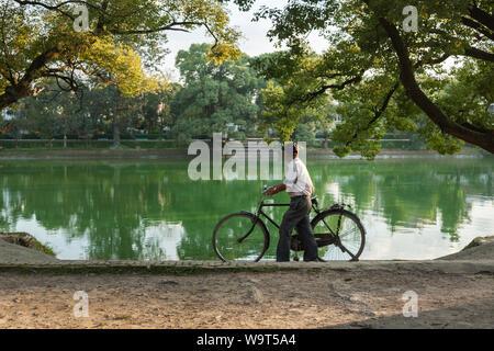 Mann mit seinem Fahrrad durch einen Park neben einem See. - Stockfoto