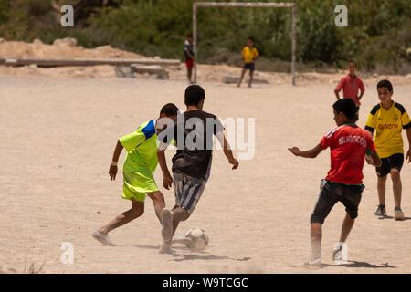 Jungen Fußball spielen in einem Feld außerhalb von Agadir, Marokko. - Stockfoto