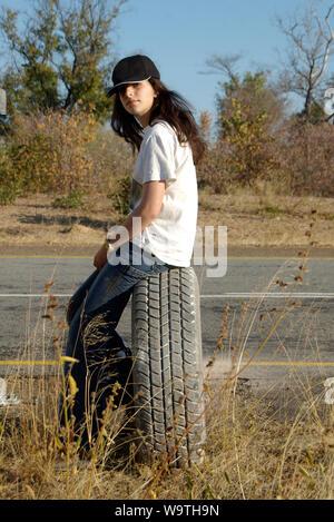 Junges Mädchen sitzt auf einem Reifen an der Seite der Straße, Namibia - Stockfoto