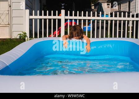Ein kleines Mädchen am Rande eines aufblasbaren Pool an einem heißen Sommertag. - Stockfoto