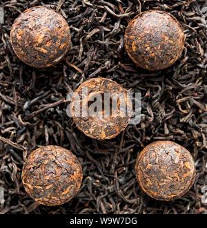 Chinesische pu-erh Tee in der Form einer Kugel des Alten duftenden Kaffee und trocken zylindrischen Steinen. Duftende schwarz PU-Erh Tee. Gesundes Getränk. - Stockfoto
