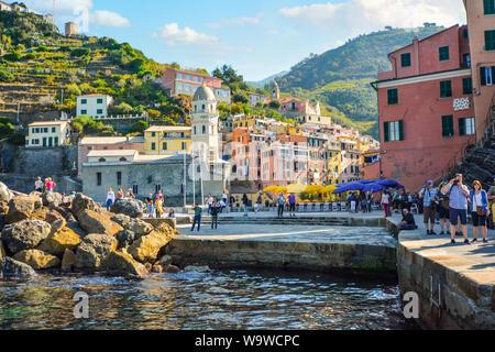 Touristen genießen das Meer, Dock und Dorf an einem Sommermorgen am Hang Stadt Vernazza Italien, Teil der Cinque Terre an der italienischen Riviera - Stockfoto