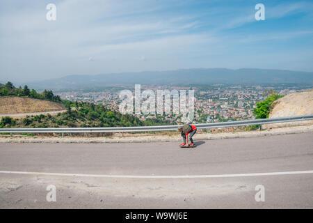 Männliche Hipster mit Hut und ein rotes Shirt ist Reiten ein Longboard downhill auf offener Straße - Stockfoto