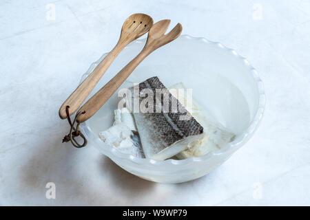 Gesalzenen und getrockneten Kabeljau (Gadus morhua) in Kunststoff Schüssel gefüllt mit Wasser zu entsalzen und gekocht und Holzlöffel auf weißem Hintergrund. Gesundes Essen. - Stockfoto