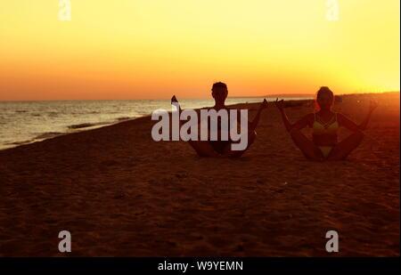 Mädchen am Strand Yoga - Stockfoto