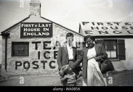 """1950, historische, eine Mutter mit ihren beiden Söhnen und außerhalb der 'Erste & letzte Haus in England"""", ein altes Landhaus, das als Kaffee und einen kleinen Laden, in dem Eis und Souvenirs an der Küste bei Lands End, Cornwall, England, Großbritannien. - Stockfoto"""