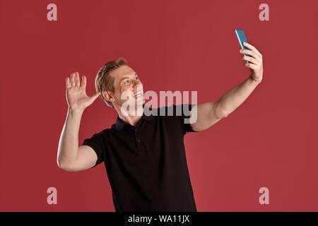 Nahaufnahme Porträt einer jungen smart Ingwer Mann in einer eleganten schwarzen T-Shirt lächelnd und winkte mit der Hand und macht ein selfie während auf Pink Studio bac Posing - Stockfoto