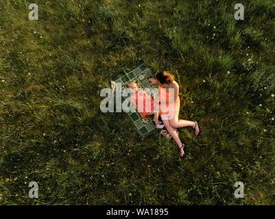Antenne: glückliche Mutter spielt mit ihrem kleinen Baby Mädchen Tochter und Spaß - Junge kaukasier weiß Mama tragen Sommer hell leuchtenden Farben Kleid - - Stockfoto