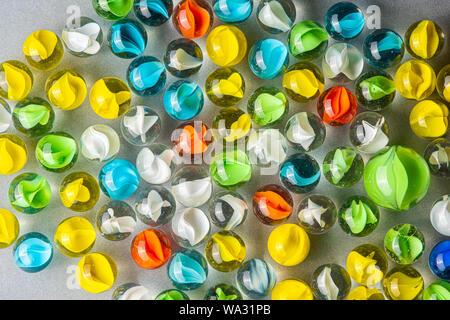 Gelb, Grün, Blau und Rot Glasmurmeln auf einen Tisch. - Stockfoto