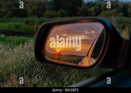 Ein Auto Außenspiegel zeigt einen goldenen Sonnenuntergang über grüne Felder hinter in einer üppigen Wiese - Stockfoto