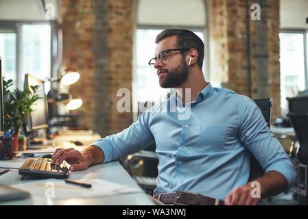 Anstrengenden Tag. Seitenansicht des Jungen bärtigen Mann mit Brille und Kopfhörer etwas Tippen auf Computer, während im modernen Büro zu sitzen. Arbeit Konzept. Business Konzept