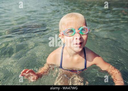 Lustige kaukasische Mädchen schwimmen im See Fluss mit Unterwasser Schutzbrille niedlich. Kind Tauchen in Wasser auf Park Beach. Authentische echten Lifestyle glücklich childhoo