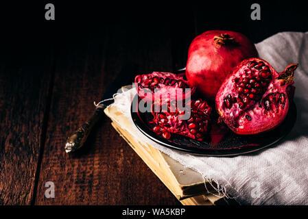 Granatapfel Obst auf Metall Platte öffnen sich über alte Bücher - Stockfoto