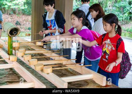 Tokyo, Japan - 14. Juni 2015 - Touristen und Besucher waschen ihre Hände und Mund am Brunnen vor dem Eintritt in den Schrein in Tokio, Japan auf Ju - Stockfoto