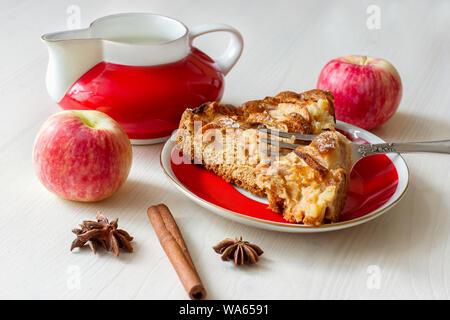 Ein Stück frischen Apfelkuchen auf dem Teller mit Gabel, frische Äpfel, Gewürze und Milchkännchen Nahaufnahme - Stockfoto