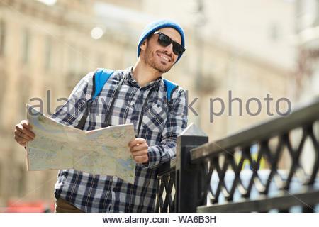 Taille bis Portrait von lächelnden jungen Mann mit Karte während der alleine unterwegs in den Straßen der alten Stadt, kopieren Raum - Stockfoto