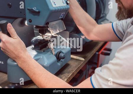 Schlosser schneiden Schlüssel mit seiner Maschine - Stockfoto