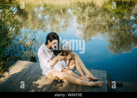 Mutter und Tochter sitzen auf einem hölzernen Brücke über einen Fluss mit Reflexion der Bäume und der Himmel im Wasser.