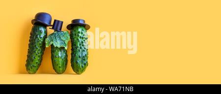 Kreative Küche Poster. Komische grüne Gurken Familie auf gelben Hintergrund. Drei lustige Gemüse mit schwarzen altmodische Hüte. Platz kopieren - Stockfoto