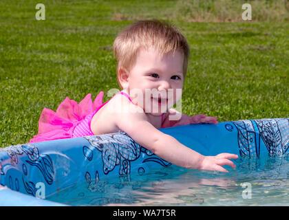 Baby Mädchen in einem rosafarbenen Badeanzug Plantschen im Kinderbecken im Freien - Stockfoto
