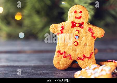 Eine traditionelle Weihnachtsplätzchen in der Form eines Menschen vor dem Hintergrund der einen Weihnachtsbaum mit einem festlichen leuchtende Girlande. - Stockfoto