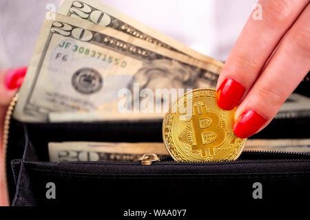 Virtuelle cryptocurrency Geld Bitcoin goldenen Münzen in der linken Hand einer Frau mit rotem Nagellack und den Geldbeutel. Die Zukunft des Geldes. US-Dollar. - Stockfoto